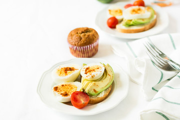 Healthy breakfast: toasts with avocado slices, tomato, paprika and eggs on white tableware. Selective focus