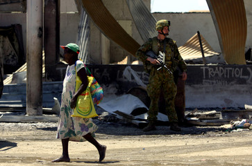 Australian soldier stands guard on a street in the Chinatown district of the Solomon Islands capital Honiara