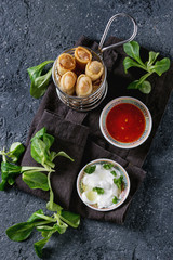 Fried spring rolls with red and white sauces, served in traditional china plate and fries basket with fresh green salad over black texture background. Flat lay, space. Asian food