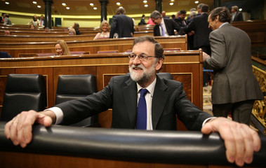 Spain's PM Rajoy smiles in his seat during the budget debate at Parliament in Madrid