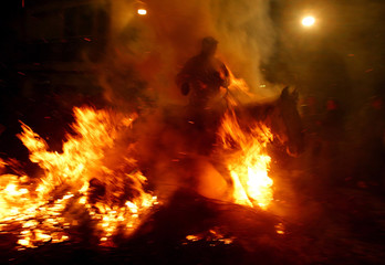A rider on horseback passes through a bonfire during the annual Saint Anthony purification ceremony ..