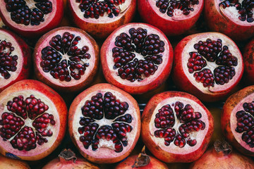 Rows of red juicy ripe sliced pomegranate on the market creating a background