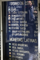 A pedestrian is reflected on boards of exchange rates at a money exchange bureau in downtown Santiago