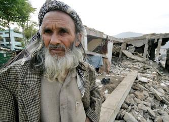 Elderly Kashmiri earthquake survivor stand near debris of destroyed his building in Bagh