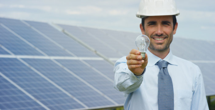Technical expert in solar photovoltaic panels, remote control performs routine actions to monitor the system using clean renewable energy in the hand a light bulb. Concept of remote support technology