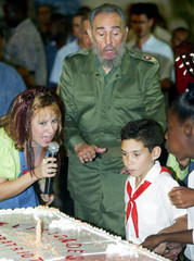 ELIAN LOOKS AT BIRTHDAY CAKE AS CUBAN PRESIDENT CASTRO LOOKS ON.