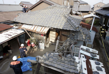 Firefighters inspect a house damaged by an earthquake in Yokkaichi, central Japan