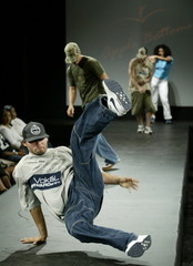 A model break dances on the runway during a presentation for Apple Bottoms clothing, created by rapp..