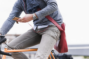 Businessman riding bicycle in the city, while using smartphone and earphones