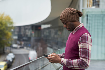 Man standing on terrace using cell phone