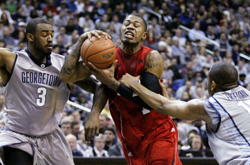 Terrence Williams of Louisville is fouled by Austin Freeman of Georgetown in Washington