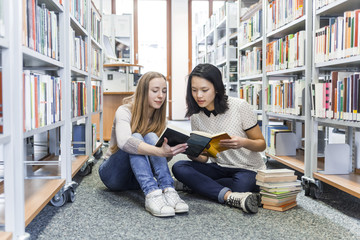 Two teenage girls sitting on the floor in a public library reading in a book
