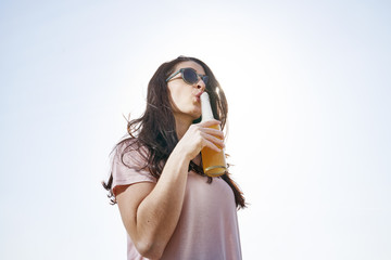 Young woman having a beer under blue sky