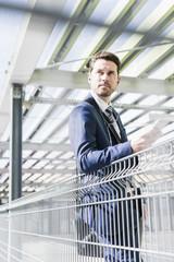 Businessman standing on parking level, portrait