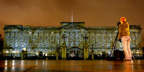 """An image showing falling snowflakes is projected onto Buckingham Palace in London as part of the """"Br.."""