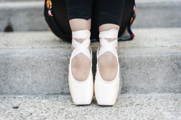 Feet of ballet dancer sitting on steps