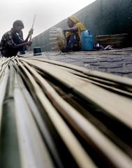 Sadri and his wife weave bamboo baskets on a bridge in Mumbai