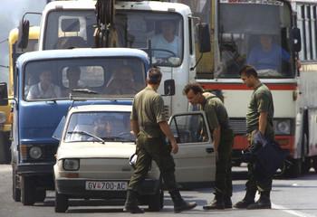 MACEDONIAN POLICEMEN CHECK A CONVOY NEAR SKOPJE.
