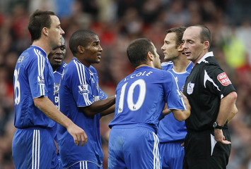 Chelsea players surround refereee Mike Dean after he sent off  team mate John Obi Mikel during their English Premier League soccer match against Manchester United in Manchester