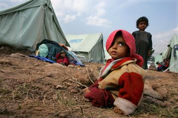 Kashmiri boy sits on ground at evacuation tent camp in Muzaffarabad