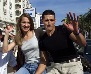 DELPHINE AND AZIZ, FORMER FRENCH TV 'LOFT STORY' PARTICIPANTS WAVE TO FANS IN CANNES.