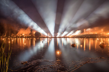 Bright light tubes over a lake with forest fire on background