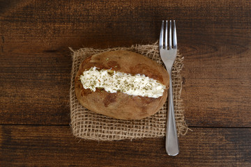 top view baked potato with sour cream and chives