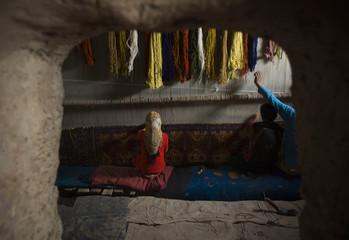 Afghans work in a carpet workshop in a village near Herat