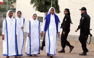 Bangladeshi Christian nuns walk as members of Rapid Action Battalion guard church in Dhaka