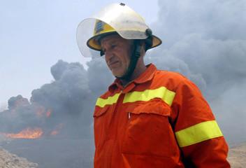 IRAQI FIREMAN WALKS PAST BURNING OIL PIPELINE BASRA.