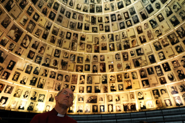 Archbishop of Canterbury Justin Welby looks at pictures of Jews killed in the Holocaust during a visit to the Hall of Names at Yad Vashem's Holocaust History Museum in Jerusalem