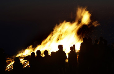 People are silhouetted in front of a fire during the midsummer festival of Sonnwendfeuer at the Bavarian mountain Kampenwand in Aschau