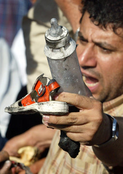 AN ANGRY PALESTINIAN YOUTH HOLDS UP A BABY'S BOTTLE AND SHOE TAKEN FROMA DESTROYED CAR IN WHICH A ...