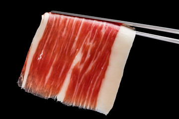Piece of cured ham on tweezers.