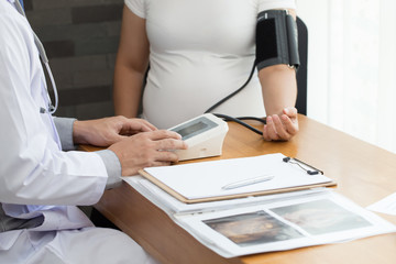 Doctor examining a pregnant woman and check blood pressure