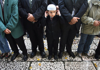 Bosnian Muslim boy and others pray outside Begova mosque in the capital Sarajevo