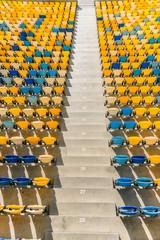 Foto auf Leinwand Stadion rows of yellow and blue stadium seats and stadium stairs