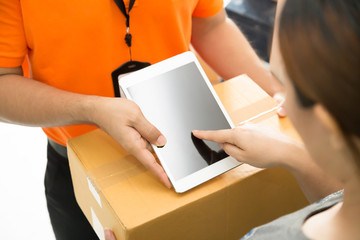 Woman appending signature on tablet after receiving parcel from courier, Delivery concept