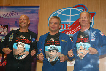 Canadian billionaire Guy Laliberte, Russian cosmonaut Maxim Surayev and U.S. astronaut Jeffrey Williams show their cartoons on the t-shirts at a news conference at Baikonur cosmodrome