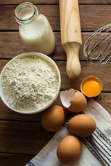 Baking ingredients flour, cracked eggs, open yolk, milk, rolling pin, linen towel, rustic kitchen interior, utensils, top view