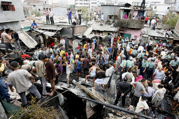 Police and onlookers gather at the site of a fire at the Mohammadpur Geneva Camp in Dhaka
