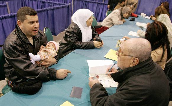 Iraqis Tahir Al Kanani, his wife Farakid Mahadi register to vote in Chicago for the Iraqi Transitional ...