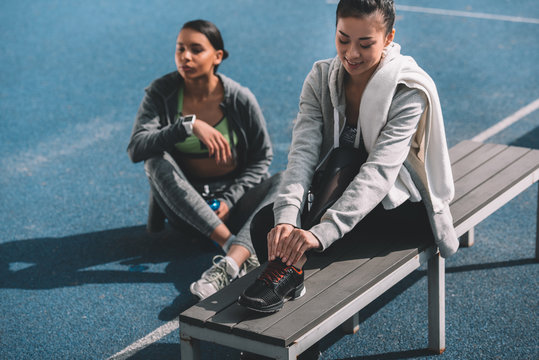 Two athletic young women in sportswear resting together on stadium