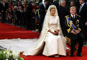 Princess Maxima (C) and Dutch Crown Prince Willem-Alexander sit side-by-side during the wedding cere..