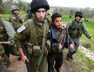 Israeli troops arrest Palestinian youth during protest in the West Bank village of Bilin.