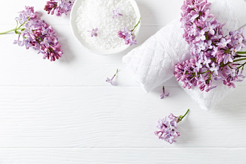 Natural bath salt, cotton towels and lilac flowers (symbolic image)