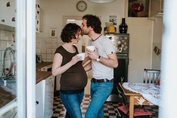 pregnant couple drinking tea in the kitchen