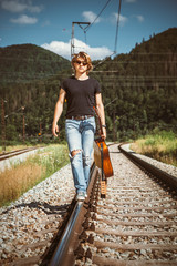 Young man with guitar walks on railways