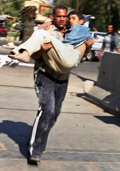 An Iraqi man brings his injured son to a hospital following a car bomb explosion in western Baghdad.