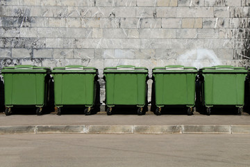 Green garbage containers standing in a row in the backyard of an industrial building.